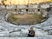 Antique Theater In The Ancient City Of Side. Roman Antique Theater. A Young Blonde With Long Hair An poster