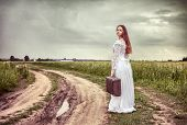 The offended bride going with an old suitcase on the rural road