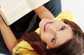 stock photo of girl reading book  - Student girl is smiling and sitting with book on her knee - JPG