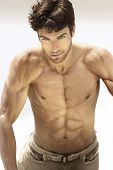 stock photo of tease  - Portrait of a sexy male model without shirt revealing very muscular body - JPG