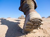 Human Foot Sole In Hiking Boot Walking On The Sand In Desert, Heel Close Up, Selected Focus poster