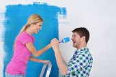 image of family fun  - happy young couple paint in green and blue color white wall of their new home - JPG