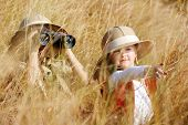 image of safari hat  - Happy young safari adventure children playing outdoors in the grass with binoculars and exploring together as brother and sister - JPG