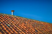 Sloping Tiled Roof Against Blue Sky With Single Metal Flue poster
