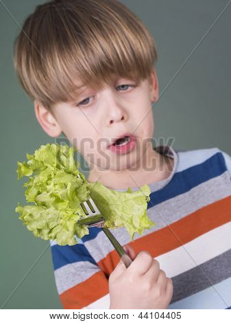 Pretty boy holding green salad on fork