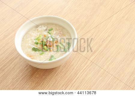 Congee bowl on wood texture tile floor.