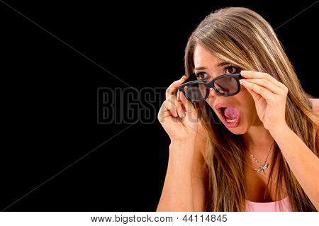 Shocked woman watching 3D movie - isolated over a black background
