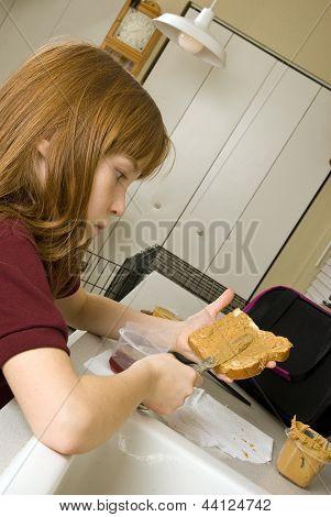 Young school girl preparing her lunch