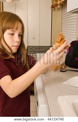Young school girl preparing her lunch