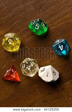 Multicolored role play dice sitting on a wooden table top