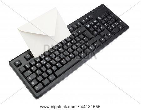 Teclado de la computadora con ensobrado para correo dentro. Aislado en blanco.