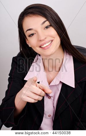 Young smiling business woman pointing finger at viewer