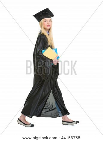 Full Length Portrait Of Young Woman In Graduation Gown With Books Going Sideways