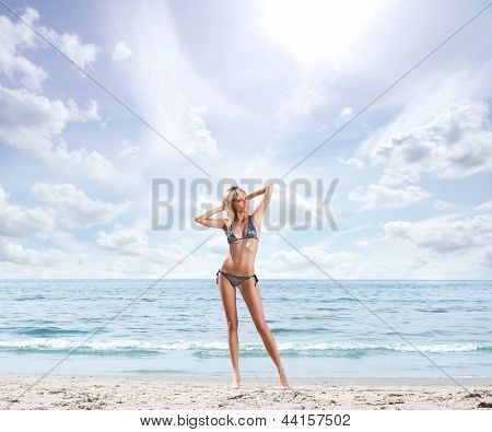 Young, beautiful, sporty and sexy blond woman relaxing on the beach