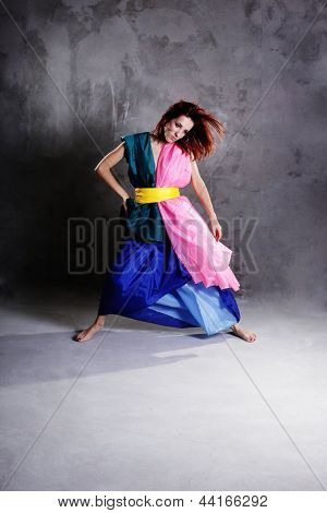 Young modern dancing girl in colorful dress on the dirty grunge grey studio background