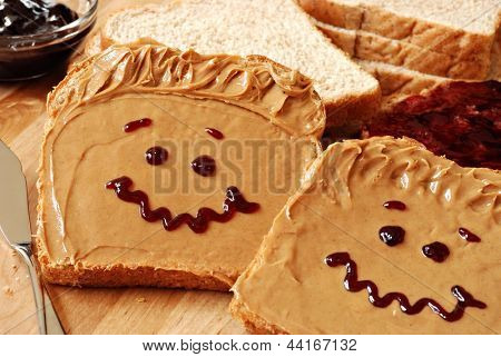 Making peanut butter sandwiches with personality! Fun smiley faces drawn on with jam. Creamy peanut butter with jam on whole grain wheat bread on wood cutting board. Macro with shallow dof.