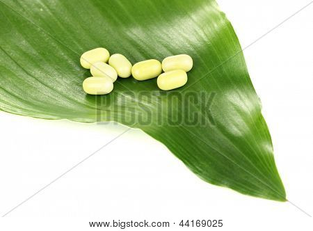 tablets on green leaf isolated on white