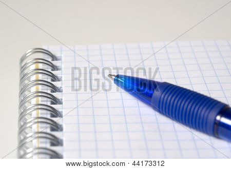 Blue pen and notebook close up