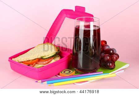 Lunch box with sandwich,grape,juice and stationery on pink background