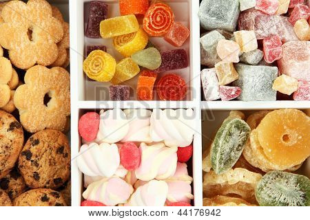 Multicolor candies and cookies in white wooden box close up