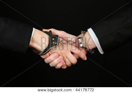 Man and woman hands and breaking handcuffs isolated on black background