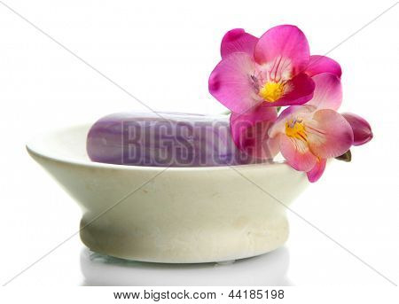 Soap-dish with soap and flower isolated on white