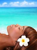 Luxury holidays, beautiful black woman lying down with closed eyes on the beach, day spa, summertime