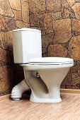 stock photo of linoleum  - Toilet room with a toilet bowl and walls from a stone and a floor from linoleum - JPG