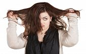 stock photo of yanks  - Woman looking over while pulling messy hair - JPG