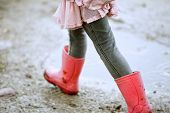 stock photo of rainy day  - Close up little girl walking outdoors with red boots - JPG