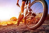 low angle view of cyclist riding mountain bike on rocky trail at sunrise