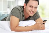 stock photo of laying-in-bed  - young asian man texting a message with his cell phone while laying on bed - JPG