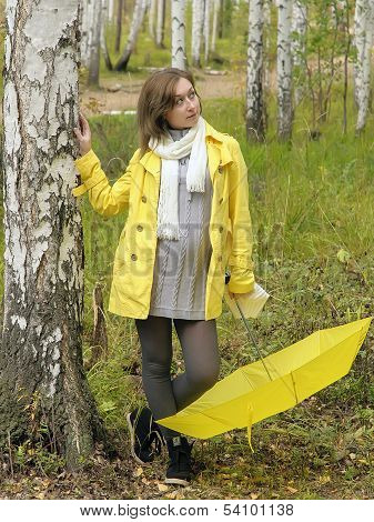 Girl in autumn forest with yellow umbrella