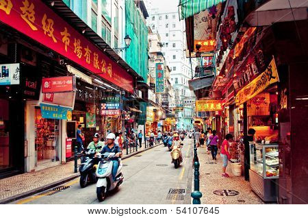 Narrow crowded street with many shops and restaurants in the centre of Macau