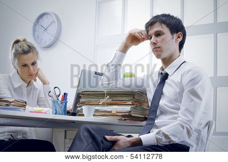 Two bored business people sitting in office