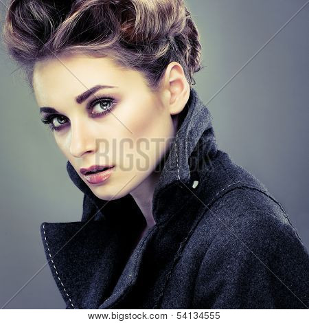 Portrait of elegant young woman in a grey overcoat  on a grey background