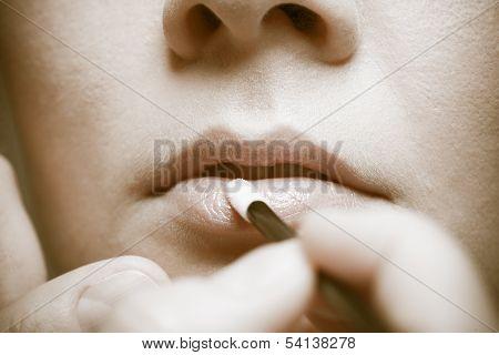 Makeup. Girl Applying Lipgloss Lipstick On Lips. Part Of Face. Sepia.