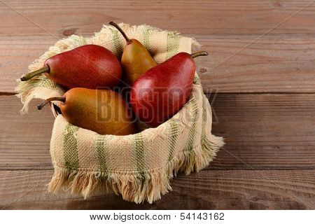 Bosc and Red Pears in a basket on a rustic wooden table. Horizontal format.