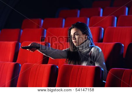 A Young Woman Holding A Tv Remote Control, In The Background You Can See The Red Chairs In A Movie T