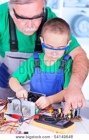 Grandfather Teaching Grandchild Measuring With Digital Multimeter