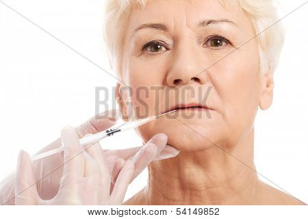An old woman having a injection- beauty concept. Isolated on white.