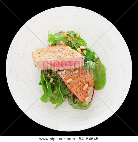 Lightly seared tuna steak with sesame and fresh salad isolated on black