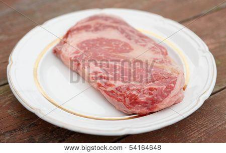 Kobe beef ribeye steak in rustic plate on wooden table