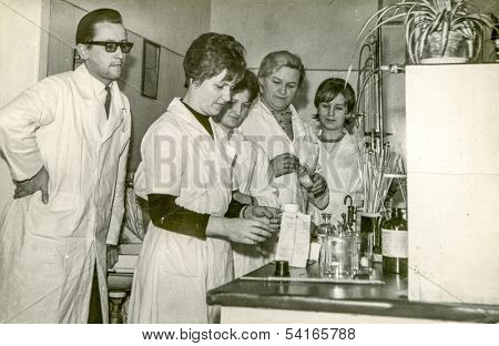 LODZ, POLAND, CIRCA 1950 - Vintage photo of group of medical university students wearing aprons during practical training, in Lodz, Poland, circa 1950