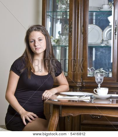 Pretty Girl Sitting At The Table