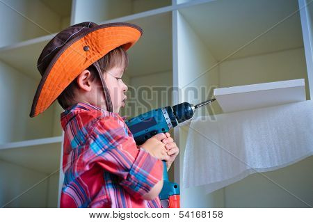 Cute little boy using an electric screwdriver