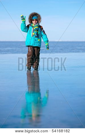 Cute little boy outdoors standing on frozen sea