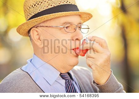 Portrait of senior man taking asthma treatment in a park