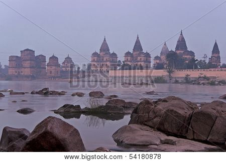 Group Of Cenotaphs In The Foggy Early Morning Across Betwa River At India's Orchha.