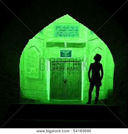 Silhouette of the tourist on the background of green illuminated oriental wall with old doors. Khiva town, Uzbekistan